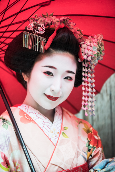 Young Japanese maiko woman with hair accessories and traditional make up smiling towards camera