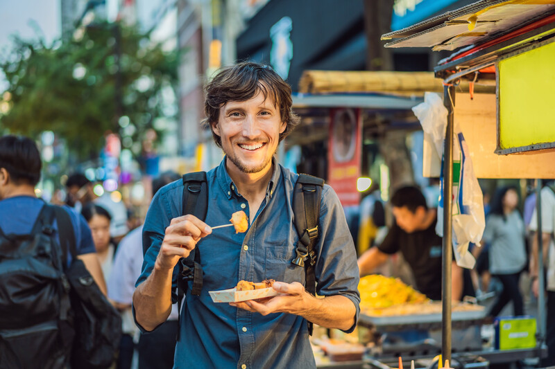 Young man tourist eating Typical Korean street food on a walking street of Seoul. Spicy fast food simply found at local Korean martket, Soul Korea.