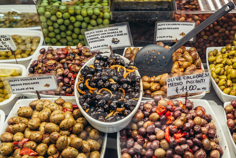 Varieties of olives for sale on covered food market - Mercato Delle Erbe in historic part of Bologna city, Italy