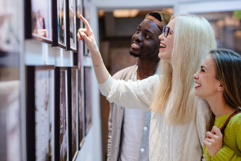 Three young people hipster students with different skins looking happy together, talkng, looking at picture on wall, spending free time together in ar