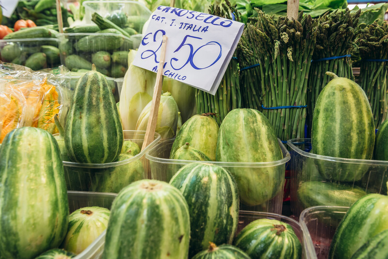 Stall with carosello melons on covered food market - Mercato Delle Erbe in historic part of Bologna city, Italy