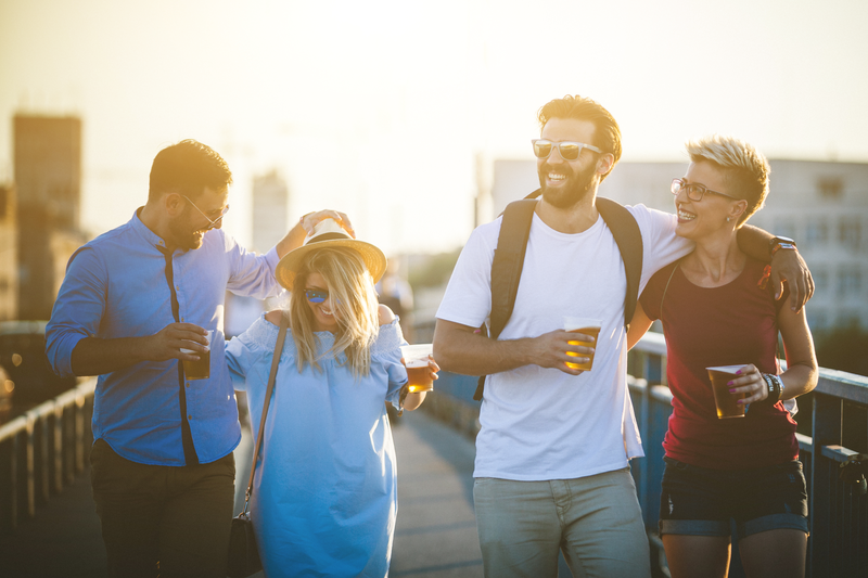 Hipster people are walking through the bridge. This group of friends are holding plastic glasses with beer in it and drinking it. They are enjoying at amazing sunset behind them. There are two men and two women who are spending great time together. It's weekend and they decide to relax and hanging out together on traveling. Everybody are dressed casual and comfortable so they are walking a lot this afternoon.